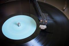 Roterend vinylverslag met blauw etiket op een draaischijfclose-up Royalty-vrije Stock Fotografie
