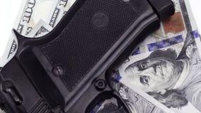 Roterende achtergrond, zwart kanon die op honderd dollarsrekeningen liggen stock footage