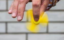 Roterende gele spinner in de mannelijke hand Royalty-vrije Stock Fotografie