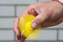 Roterende gele spinner in de mannelijke hand Stock Fotografie