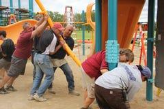 Roterende leden van de gemeenschap die een speelplaats voor kinderen helpen te bouwen stock afbeelding
