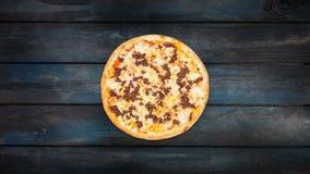 Roterende pizza met gehakt op een donkere houten achtergrond De hoogste richtlijn van het meningscentrum stock videobeelden