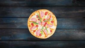 Roterende pizza met ham, paprika, rucola, tomaten en ijsbergsla op een donkere houten achtergrond stock footage