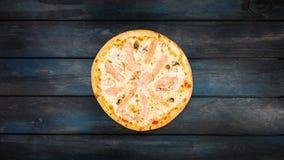 Roterende pizza met zeevruchten op een donkere houten achtergrond De hoogste richtlijn van het meningscentrum stock videobeelden