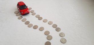 Rotes abarth Fiats 500 Spielzeug, das seine Weise auf der Straßenlinie gemacht ein-von den israelischen Schekel-Münzen beginnt stockfotos