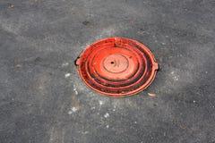 Rotes Abwasserkanaleinsteigeloch Stockfoto