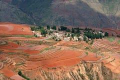 Rotes Ackerland mit Dorf in dongchuan des Porzellans Lizenzfreie Stockfotografie