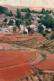 Rotes Ackerland mit Dorf in dongchuan des Porzellans Stockbilder
