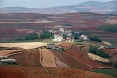 Rotes Ackerland mit Dorf in dongchuan des Porzellans Lizenzfreies Stockfoto