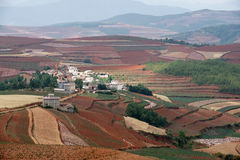 Rotes Ackerland mit Dorf in dongchuan des Porzellans Lizenzfreies Stockbild