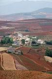 Rotes Ackerland mit Dorf in dongchuan des Porzellans Stockfoto