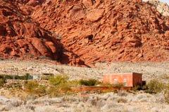 Rotes Adobe-Haus in der Wüste durch Mountains Lizenzfreies Stockfoto