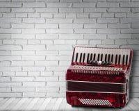 Rotes Akkordeon der Weinlese auf Backsteinmauerhintergrund lizenzfreie stockfotos