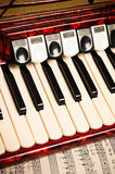 Rotes Akkordeon und Noten stockfoto