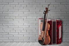 Rotes Akkordeon und Violine der Weinlese auf Backsteinmauerhintergrund stockfotos