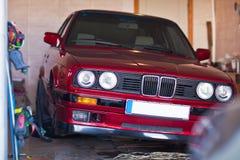 Rotes altes Auto in einer Garage ohne ein Rad Stockfotos