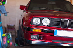 Rotes altes Auto in einer Garage ohne ein Rad Stockfoto
