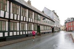 Rotes altes Haus mit weißen Fenstern - Fachwerkhaus gemacht vom Holz und von den Ziegelsteinen Fahrrad nahe der Wand lizenzfreies stockbild
