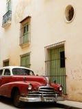 ROTES AMERIKANISCHES AUTO UND GRÜNE TÜREN UND WINDOWS, HAVANA, KUBA Stockbild