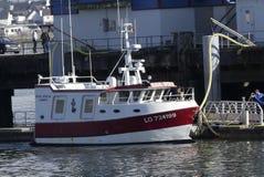 Rotes anf weißes Fischerboot koppelte am Pier an Stockfotos