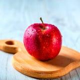 Rotes Apple auf hölzernem Brett Stockbilder