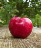 Rotes Apple auf hölzerner Tabelle Lizenzfreie Stockfotografie