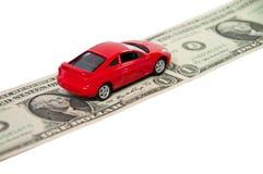 Rotes Auto auf Dollarbezeichnungen Stockfotografie