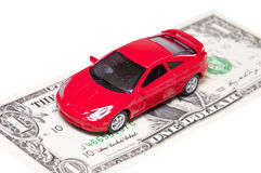 Rotes Auto auf Dollarbezeichnungen Stockfotos