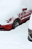 Rotes Auto bedeckt mit Schnee im Winterblizzard Lizenzfreie Stockfotos