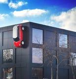 Rotes Auto befestigt auf einer Wand des schwarzen Hauses Stockfotos