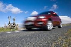 Rotes Auto, das auf leere Gebirgsstraße beschleunigt Stockfotografie