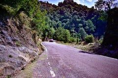Rotes Auto, das durch eine Straße in den Bergen im Urlaub fahren rotes Auto durch die Hügel reisen in das Himalaja-mountai beschl stockfotografie