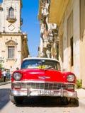 Rotes Auto der Weinlese auf einer schmalen Straße in altem Havana Lizenzfreie Stockfotos