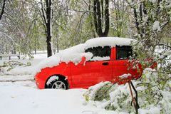 Rotes Auto in einem Parkplatz, umfasst mit Schnee während eines snowfal Stockfotografie