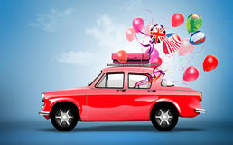 Rotes Auto mit Symbolen der Liebe, des Feiertags, des happyness und der Reise. Stockbild