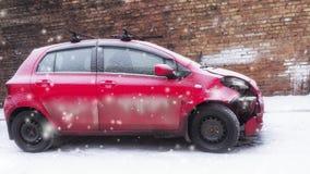 Rotes Auto nach dem Unfall gegen eine Backsteinmauer im Winter stock video