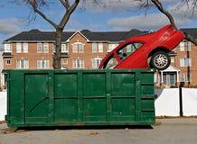 Rotes Auto und grüner Müllcontainer Stockbild