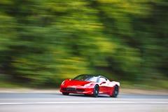 Rotes Autoauf Landstraße schnell fahren Stockbilder