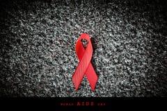 Rotes Band des roten Bandes auf einem Stein, Welt-Aids-Tag-Konzept Stockfoto