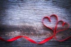 Rotes Band machte Herzform auf hölzernem Hintergrund Konzept Valent Stockbild