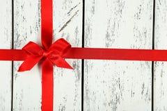 Rotes Band mit Bogen auf weißem hölzernem Hintergrund Lizenzfreie Stockfotos
