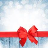 Rotes Band mit Bogen über Weihnachtsschnee-Holzhintergrund Stockfoto