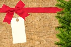 Rotes Band mit einem Tag und Weihnachtsbaumast auf hölzernem backgr Lizenzfreies Stockfoto