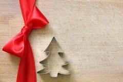Rotes Band und Bogen auf Weinleseschneidebrett-Weihnachtshintergrund Stockbilder
