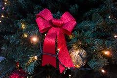 Rotes Band und goldener Ball auf Weihnachtsbaum Stockfotos