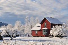 Rotes Bauernhaus mit frischem Winterschnee und -frost Lizenzfreies Stockbild
