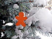 Rotes Baumspielzeug im Schutz des Schnees Stockbilder