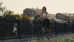 Rotes behaartes Frauenreitfahrrad in der Stadt auf Hintergrundfassadengebäude stockfotografie