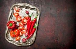 Rotes biologisches Lebensmittel Frischer Pfeffer, Tomaten und Gemüsepaprika des scharfen Paprikas auf einem Stahlbehälter Lizenzfreies Stockfoto