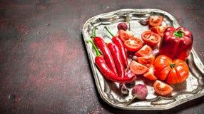 Rotes biologisches Lebensmittel Frischer Pfeffer, Tomaten und Gemüsepaprika des scharfen Paprikas auf einem Stahlbehälter Stockfotos